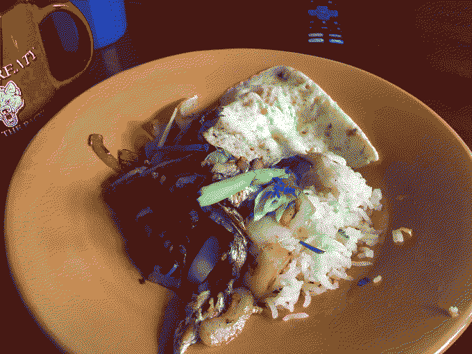 A plate of sauteed sardines with rice and egg.