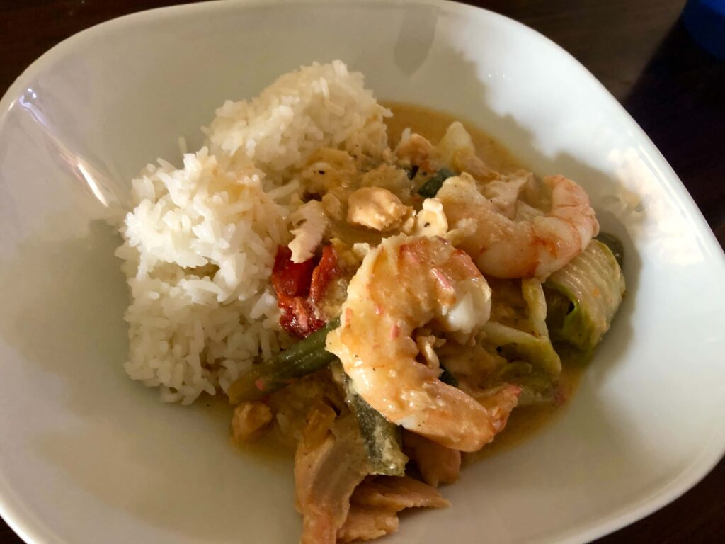 A bowl of rice with shrimp, salmon, and veggies in coconut milk.