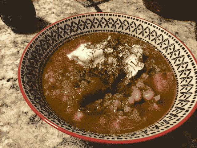 A bowl of North African bean stew with visible peppers, yogurt, and fennel fronds visible.